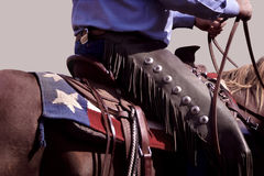 Texas Cowboy. Cowboy wearing chaps on horse with design of Texas flag on saddle blanket Stock Photo