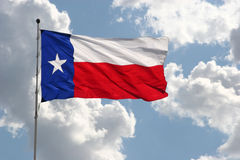 Texas flag. On clouds and sky stock images