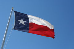The texas flag. Flying in a blue sky royalty free stock photography