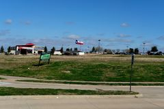 Texas flag blowing in the wind. Texas flag blowing in the wind at a distance, in a commercial lot and mall parking lot on a clear day royalty free stock photos