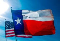 Texas Flag drog tillbaka vid amerikanska flaggan Arkivfoto
