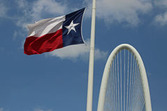 Texas Flag fluttering. Texas Flag against blue sky with bridge in background stock images