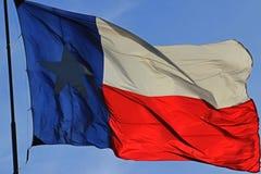 Texas Flag in full sunlight. Texas flag fluttering in evening sky against sunset stock photo