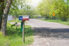 Texas flag painted on the mailbox. Mailbox painted with a Texas flag along a country road. Lush green trees in the background stock image
