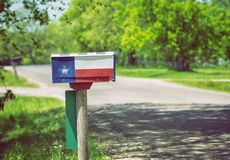 Texas flag painted on the mailbox. Mailbox painted with a Texas flag along a country road. Lush green trees in the background royalty free stock photography