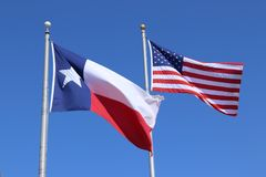Texas flag, Lone Star State flag and United States of America US flag against clear blue sky background royalty free stock photos