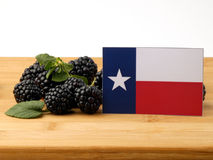 Texas flag on a wooden panel with blackberries isolated on a whi royalty free stock image