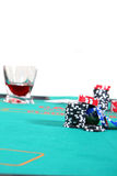 Texas Hold'Em. A poker table with chips a drink and cards. Isolated over white Stock Image
