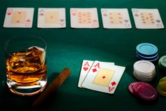 Texas hold`em poker with a hand of two aces. Chips, cigar, and glass of whiskey on green broadcloth. Won by three aces stock photo