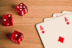 Texas holdem with dice and cards. Detail of red dice and cards on old wood Stock Photography