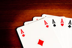 Texas holdem with poker aces. Detail of poker aces on old wood Royalty Free Stock Image