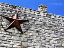 Texas Lone Star on brick building, Austin. Bronze star installed on gray brick wall with chimney against bright blue sky on store in Austin, Texas royalty free stock photos