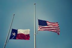 Texas och Förenta staternaflaggorna på halva stången royaltyfri foto