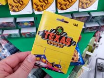 Texas Roadhouse gift card in a hand. PLATTSBURGH, USA - JANUARY 21, 2019 : Texas Roadhouse gift card in a hand over a shelves with different giftcards in a royalty free stock photography