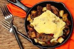 Texas Skillet Breakfast mit Steak, Kartoffel und Ei Lizenzfreies Stockfoto