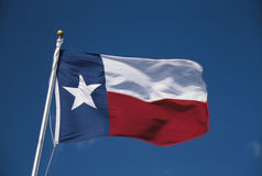 Texas State Flag. This is the Texas State Flag flying in the wind. it is on a flagpole against a blue sky. There is a single white star on the left hand side stock photography