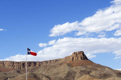Texas State Flag against Blue Sky with Rock Mesa. Flag from the state of Texas against a blue sky in the shadows of rock mesa with copy space stock photography