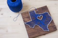 Texas State String Art. String art in the shape of Texas on a wooden background Royalty Free Stock Images