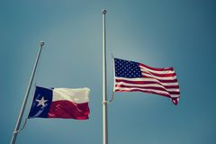 Texas and the United States flags at half-mast. The state flag of Texas and the United States flag flying at half-mast or half-staff on a flagpole. Blue sky royalty free stock photo