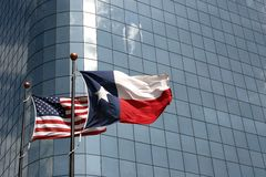 Texas and USA flags. Texas and United States flags in front of an office building royalty free stock photography