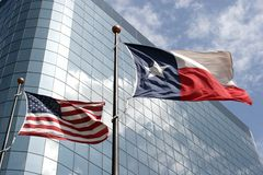 Texas and USA flags. Texas and United States flags in front of an office building royalty free stock photo