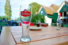 Empty glass of Dutch Texel Skuumkoppe wheat beer standing on table in beer garden royalty free stock image