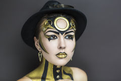 Texno girl. Techno golden girl with bright makeup. Streams of gold, shiny cheeks, black steam punk hat, big circle on forehead, body art. Sexy lips, decorations Stock Photography