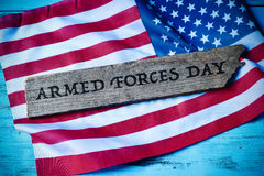 Text armed forces day and flag of the United States. The text armed forces day written in a piece of wood and a flag of the United States, on a blue rustic Stock Images