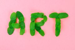 The text of art is laid out of mint leaves on a pink pastel background. The text of art is laid out of mint leaves on a pink pastel background royalty free stock image