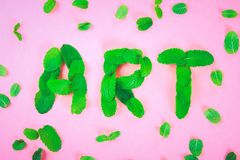 The text of art is laid out of mint leaves on a pink pastel background. The text of art is laid out of mint leaves on a pink pastel background stock photography