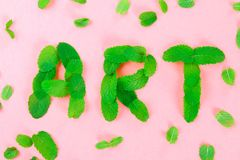 The text of art is laid out of mint leaves on a pink pastel background. The text of art is laid out of mint leaves on a pink pastel background royalty free stock photos
