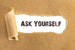 The text ASK YOURSELF appearing behind torn brown paper.  Royalty Free Stock Photography