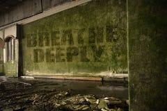 Text atmen tief auf der schmutzigen Wand in einem verlassenen ruinierten Haus Lizenzfreies Stockbild