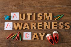 Text AUTISM AWARENESS DAY on background. Text AUTISM AWARENESS DAY on wooden background Stock Images