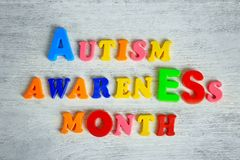 Text AUTISM AWARENESS MONTH. On wooden background royalty free stock photo