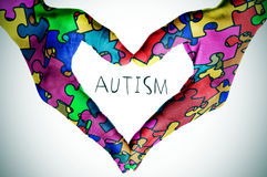 Text autism and hands forming a heart with puzzle pieces. Woman hands forming a heart patterned with many puzzle pieces of different colors, symbol of the autism royalty free stock image