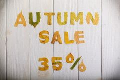 Autumn sale 35 percent. The text `autumn sale 35 percent,` cut from different yellow and orange fallen leaves from the trees and laid on the white wooden boards Royalty Free Stock Photos