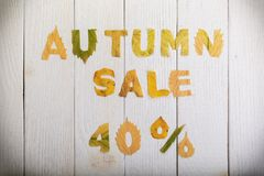 Autumn sale 40 percent. The text `autumn sale 40 percent,` cut from different yellow and orange fallen leaves from the trees and laid on the white wooden boards Royalty Free Stock Image