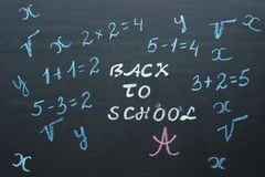 Text Back to school and mathematical examples on black chalkboar royalty free stock image