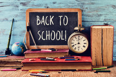 Text back to school written on a chalkboard. A chalkboard with the text back to school, some old books, an old clock, some pencil crayons and other old royalty free stock photos