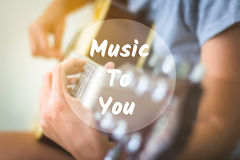 Text background music to you on a woman playing guitar. Royalty Free Stock Images