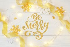 Text Be Merry in Christmas garland of garlands and snowflakes on a wooden background. Photography for holiday greeting. Card invitation calendar poster banner stock photo