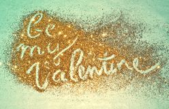 Text Be My Valentine of golden glitter sparkles on blue background. For your design Royalty Free Stock Photo
