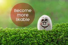 Become more likable. The text Become more likable with stone smile happy face on green moss and sunshine light background stock image