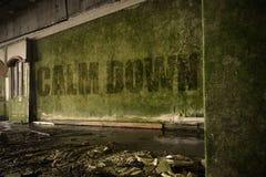Text beruhigen sich auf der schmutzigen Wand in einem verlassenen ruinierten Haus Lizenzfreies Stockfoto