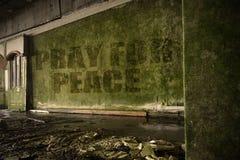 Text beten für Frieden auf der schmutzigen Wand in einem verlassenen ruinierten Haus Lizenzfreie Stockfotografie