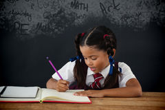 Composite image of text on black chalkboard. Text on black chalkboard against schoolgirl doing her homework against chalkboard Royalty Free Stock Photos