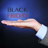 Text black friday in the hand of a businessman. The hand of a young caucasian man wearing a gray suit and the text black friday on a black background lightened Royalty Free Stock Photos