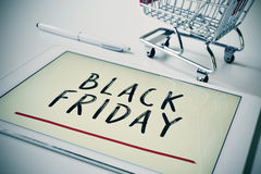 Text black friday in a tablet and a shopping cart Royalty Free Stock Photos