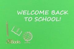 Text a boa vinda de volta à escola, miniaturas de madeira das fontes de escola no fundo verde fotografia de stock
